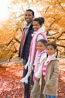 Portrait of family standing in park with autumn leaves