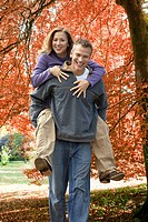 Portrait of man piggybacking woman in park