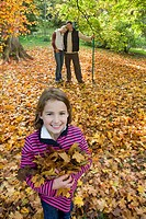 Portrait of girl holding autumn leaves with parents in background