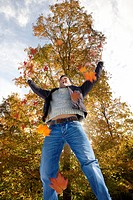 Man jumping and throwing autumn leaves