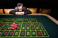 Businessman looking at pile of gambling chips on roulette table