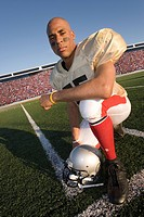 Portrait of football player kneeling on field
