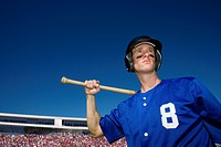 Baseball player holding bat with crowd in background