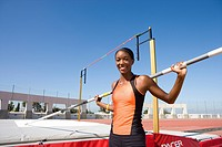 Young female pole vault athlete with pole by bar, smiling, portrait