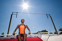 Female pole vault athlete, low angle view lens flare