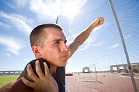 Male athlete preparing to throw shot put ball, low angle view lens flare