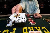 Man gambling at poker table, holding out cards, mid section (thumbnail)