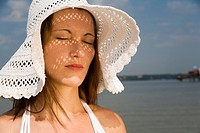 Elegant young lady (30) with white sun hat, closed eyes and relaxed face expression enjoys the summer at the bathing beach Wannsee, Berlin, Germany, E...