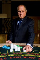 Mature man placing gambling chips on poker table, portrait (thumbnail)
