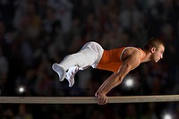 Male gymnast performing on parallel bars, side view