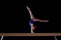 Young female gymnast 9-11 performing handstand on balance beam, side view (thumbnail)