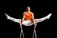 Male gymnast performing on parallel bars, low angle view (thumbnail)