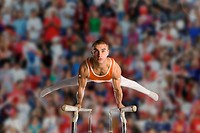 Male gymnast performing on parallel bars