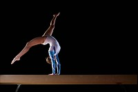 Female gymnast performing on balance beam, low angle view