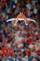 Male gymnast performing on gymnastic rings, low angle view (thumbnail)