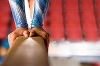 Young female gymnast performing on balance beam, low section