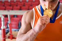 Male gymnast kissing gold medal around neck, close_up