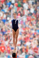 Female gymnast performing on balance beam, portrait, low angle view