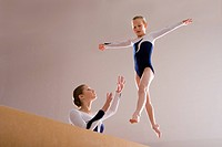 Gymnastics instructor teaching girl 5_7 on balance beam, low angle view