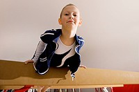Girl 5_7 on balance beam in gymnasium, smiling, portrait, low angle view