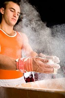 Male gymnast coating hands in powder, low angle view