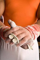 Male gymnast powdering hands, mid section
