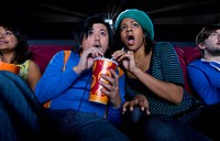 Couple in cinema sharing drink, making faces, low angle view