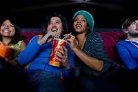 Couple sharing drink in cinema, smiling, low angle view (thumbnail)