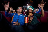 Couple in cinema wearing 3D glasses, smiling, low angle view (thumbnail)