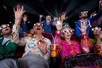 Movie audience in 3D glasses, making faces, arms raised, low angle view
