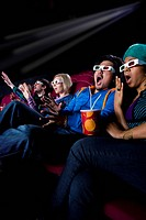 Audience in cinema wearing 3D glasses, making faces, low angle view