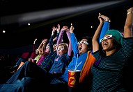 Audience in cinema wearing 3D glasses, arms raised, low angle view