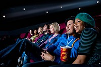 Audience in cinema, girl with drink, smiling, low angle view (thumbnail)