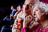 Senior couple sharing drink in cinema, close_up