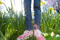 Close up of girl's sneakers and decorated Easter eggs