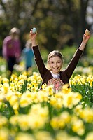 Young girl finding Easter eggs in field of daffodils