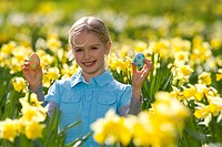 Young girl holding decorated Easter eggs in field of daffodils