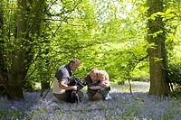 Family sitting in field of bluebell flowers