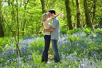 Couple kissing in field of bluebell flowers