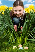 Girl finding easter eggs in grass