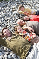 Portrait of three generation family lying on beach, high angle view