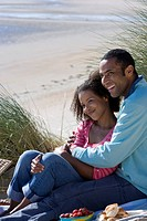 Couple sitting on beach, side view