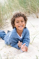Portrait of boy lying on beach
