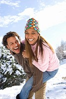 Portrait of happy mixed race couple in snow (thumbnail)