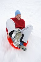 Mid adult man sledding down snow slope
