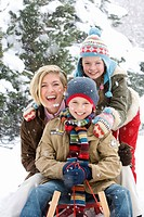 Portrait of mother and children sitting on snowsled