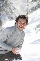 Portrait of mature mixed race man with snowball (thumbnail)
