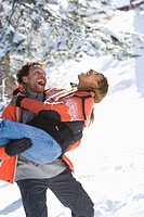 Playful mixed race couple in snow, man carrying woman