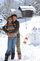 Portrait of mixed race couple standing in snow with snowman