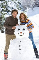 Portrait of mixed race couple with snowman